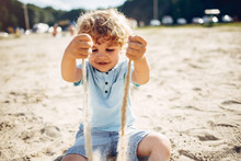 Beautiful Little Boy In A Blue Shirt. Childred Playing In A Summer Beach. On A Sand