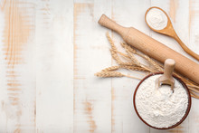 Bowl With Flour And Rolling Pin On White Wooden Background