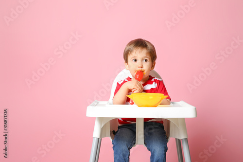 Fotomural  Cute little boy eating tasty baby food against color background