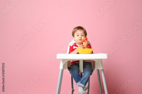 Fotografía  Cute little boy eating tasty baby food against color background