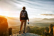 Leinwanddruck Bild - woman with camera enjoying sunset on top of mountain