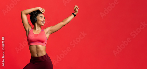 Joyful sporty girl with headset dancing over red background