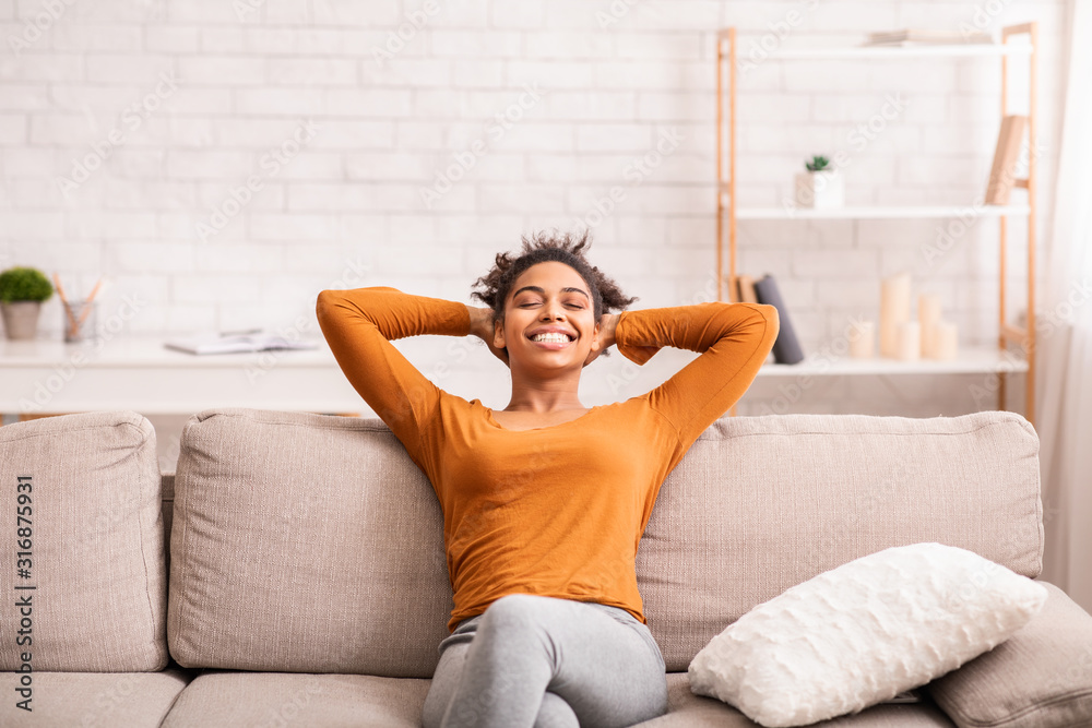 Fototapeta Happy Black Woman Relaxing Sitting On Sofa At Home
