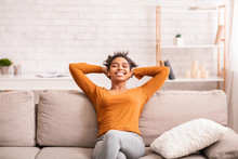 Happy Black Woman Relaxing Sitting On Sofa At Home