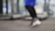 Person doing cardio exercises in fitness gym, blurry view. Unfocused view of professional athlete training indoor. Man intense training and jumping rope