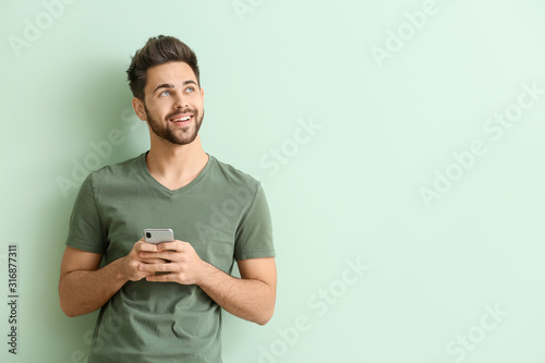 Fototapeta Happy young man with mobile phone on color background obraz