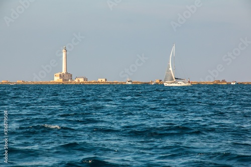 Photo Sailboat near lighthouse  (St Andrea Island), Gallipoli, Salento, South Italy