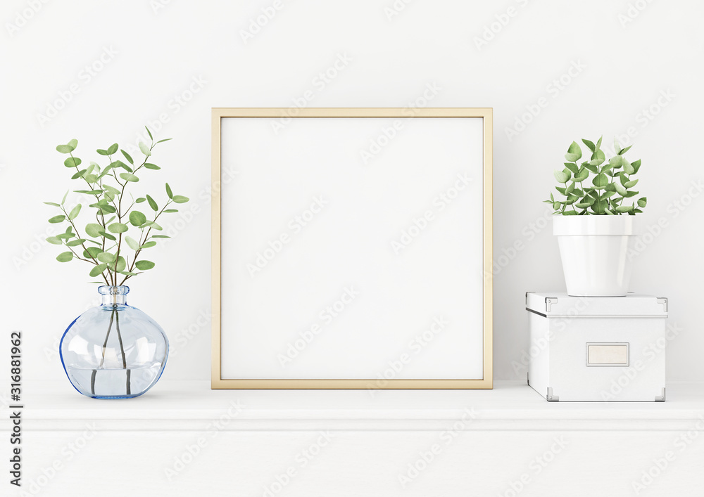 Fototapeta Interior poster mockup with square gold metal frame on the table with plants in blue vase, pot and box on empty white wall background. 3D rendering, illustration.