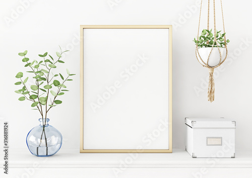 Fotografía Interior poster mockup with vertical gold metal frame on the table with plants in blue vase and hanging macrame pot on empty white wall background