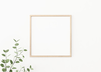 Interior poster mockup with square wooden frame on empty white wall decorated with plant branch with green leaves. 3D rendering, illustration.