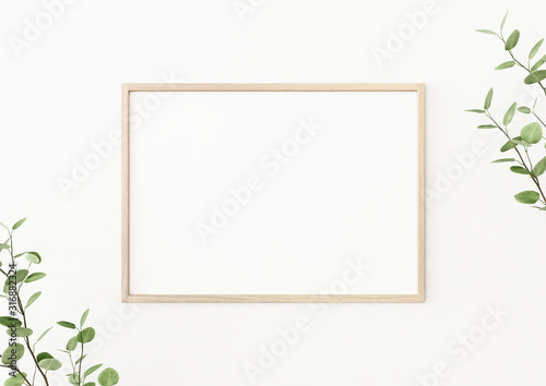 Interior poster mockup with horizontal wooden frame on empty white wall, decorated with plant branches with green leaves Wallpaper Mural