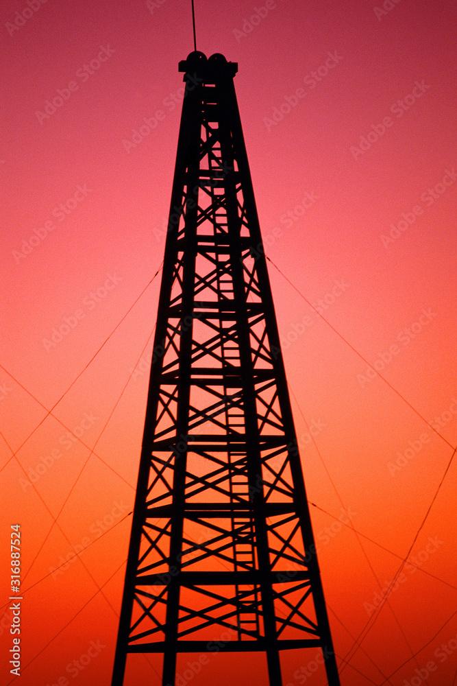 Fototapeta Oil drilling rig at sunset