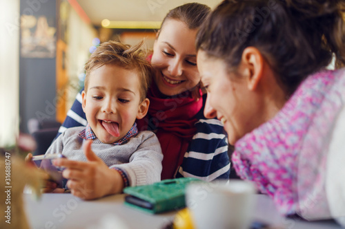 Small little boy caucasian child son sitting in the lap of his mother or aunt wo Canvas Print