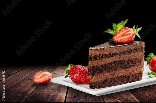 Fotografiet Slice of delicious chocolate cake on desk