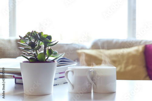 Fototapeta Relaxing sofa area with coffee table and hot drink in modern home interior obraz