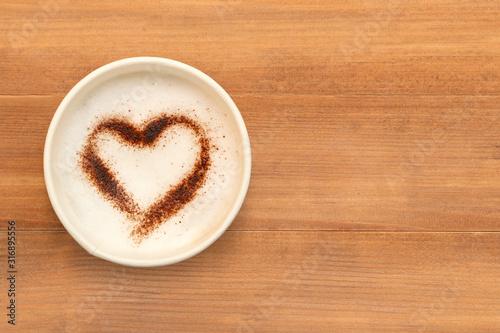 Widok z góry filiżankę kawy cappuccino z czekoladą w kształcie serca w proszku na brązowy drewniany stół