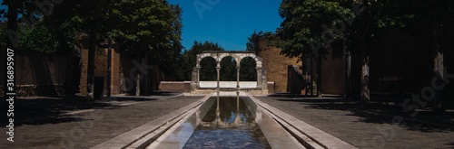 Panoramic shot of a narrow pool towards the gateway in Albi, France Canvas Print