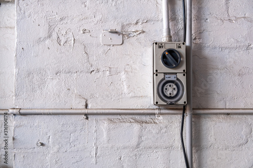 Industrial 10 amper power outlet mounted to a workshop wall with copy space Canvas Print