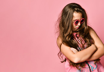 Portrait of young plus size girl with long hair in stylish summer casual clothing and sunglasses feeling displeased