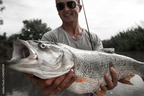 Photo Amateur angler stands in the boat, smiles and holds the trofy Asp fish (Leuciscu