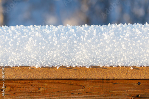 Photo Several inches of fresh cold snow and frost accumulated on a wooden fence or dec