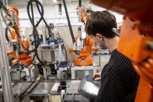 Cuadros en Lienzo Young man programming industrial automatic robot in automotive industry