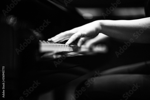 Photo Grey scale shot of a the hands of a person playing the piano