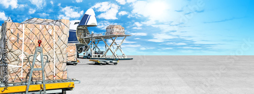 Fotografija loading cargo airplane on airport runway ultra wide panorama landscape with freight containers and shipping packages on foreground against blue clouds sky background