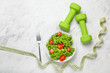 canvas print picture Healthy salad with measuring tape and dumbbells on light background. Diet concept