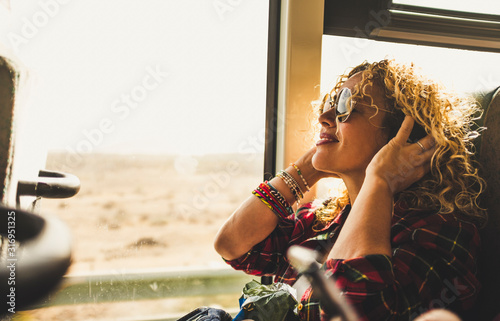 Beautiful blonde adult woman enjoying the travel on bus or train listening music with headphones - wanderlust lifestyle and happy people doing trip - happy people and transport