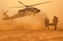 Army Soldiers Carrying Patient To The Aircraft In The Desert In Battle Field