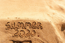 Summer 2020 Text Written On Sand On The Ocean Beach. Travel To The Tropics And Sea