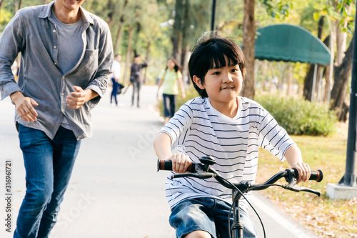 Obraz Happy Asian boy riding a bicycle with his father running behind to keep his kid safe and support at park, Dad teach son lesson and spend time together on weekend concept - fototapety do salonu