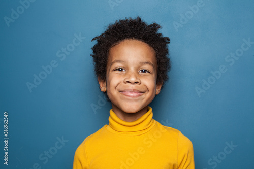Happy child portrait. Little african american kid boy on blue background