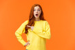 Speechless and impressed gorgeous fashionable redhead girl, young modern woman red hair, drop jaw, gasping astonished, stare camera and pointing left at interesting, awesome product