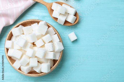 Fotografia Refined sugar cubes on blue wooden table, flat lay