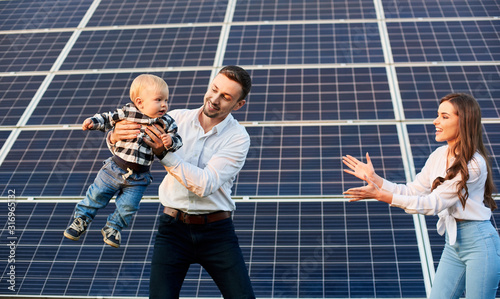 Fototapeta Happy young family with a little blond child having fun on the background of solar panels. A modern world with continuously advancing technology obraz