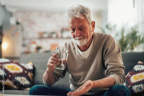 Fototapeta Old man taking pills. Senior drinking medicine.  obraz
