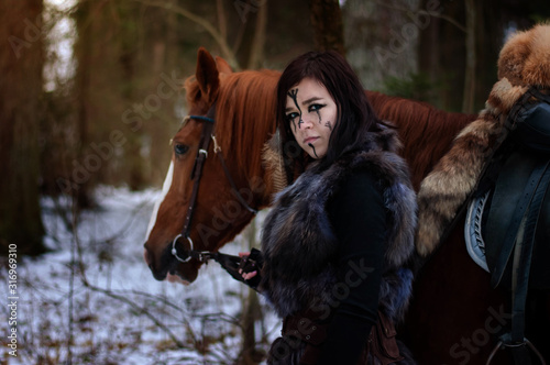 Photo a Viking girl next to a red horse painted in black runes.