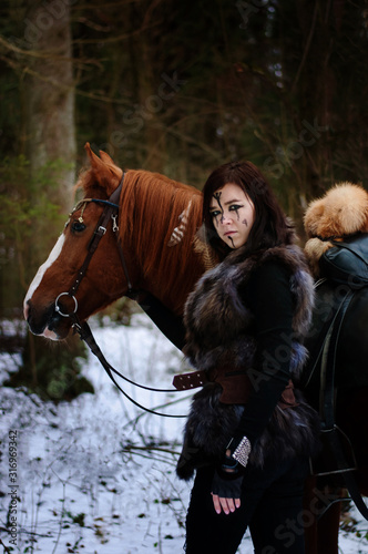 a Viking girl next to a red horse painted in black runes. Canvas Print
