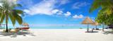 Panorama piękna plaża z białym piaskiem, turkusowym oceanem i błękitnym niebem z chmurami w słoneczny dzień. Letni tropikalny krajobraz z zielonymi palmami i słomianymi parasolami z pustą przestrzenią na kopię.