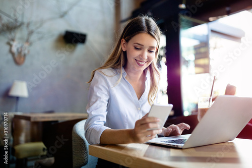 Obraz Portrait of cheerful coworker business woman working on laptop - fototapety do salonu