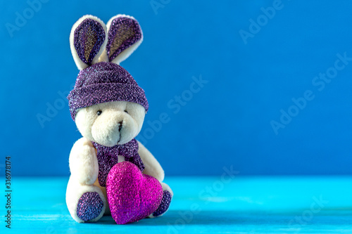 Toy bunny with a pink heart. On a classic blue color background. Selective focus.