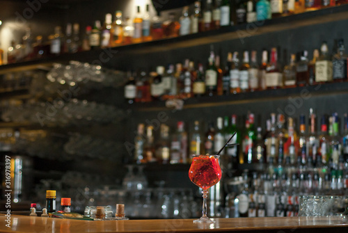 Red cocktail on bar counter. Drink with martini, gin, rum, tequila and fruit on the background of bottles with alcohol. Glass with booze on a wooden board.