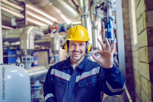 Fotografering Smiling satisfied blue collar worker in working clothes, with helmet and hardhat standing in factory and showing okay sign