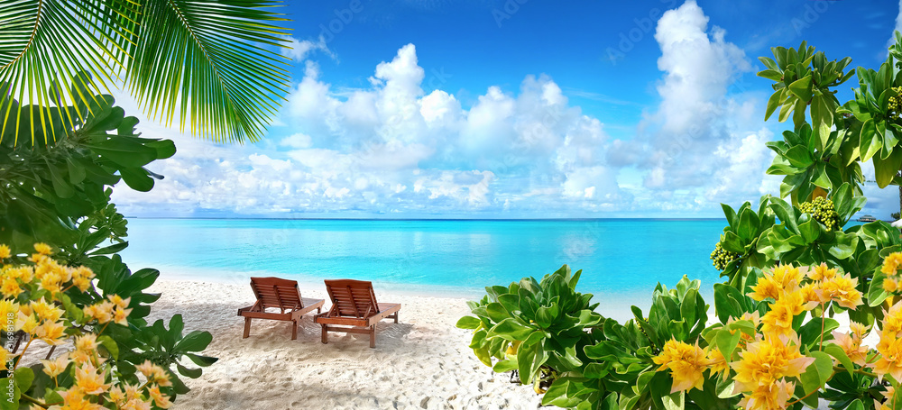 Fototapeta Beautiful tropical beach with white sand and two sun loungers on background of turquoise ocean and blue sky with clouds. Frame of palm leaves and flowers. Perfect landscape for relaxing vacation.