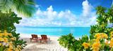 Fototapeta Fototapety z morzem do Twojej sypialni - Beautiful tropical beach with white sand and two sun loungers on background of turquoise ocean and blue sky with clouds. Frame of palm leaves and flowers. Perfect landscape for relaxing vacation.