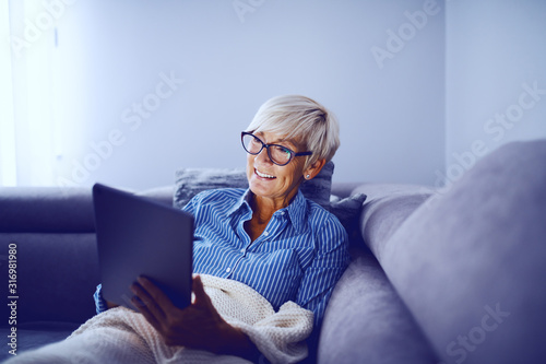 Attractive caucasian smiling blonde senior woman sitting on sofa in living room, using tablet and enjoying sunday afternoon Wallpaper Mural