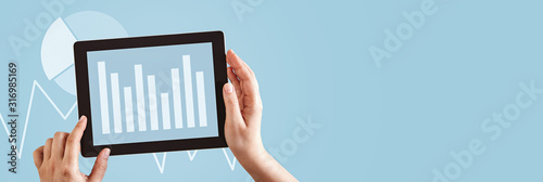 Fotografiet Hands using tablet computer analyzing business graphs on blue copy space web banner background