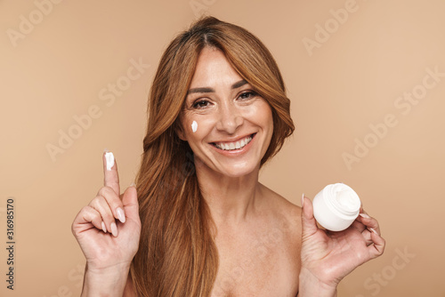 Photo Portrait of shirtless adult woman applying face cream and smiling